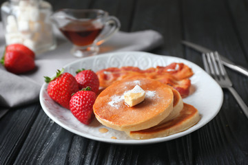 Tasty breakfast with pancakes, bacon and strawberry on plate