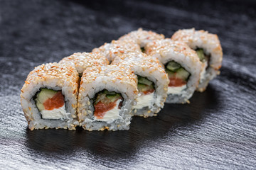 Mon roll california with salmon over slate plate background