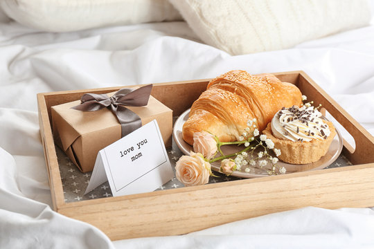 Wooden tray with breakfast and gift for Mother's day served in bed