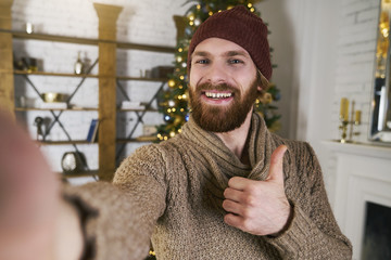 Handsome young man making selfie on christmas party with christmas tree. Man speaking online with smatphone or tablet on new year party. Congratulation friends. Always online concept.