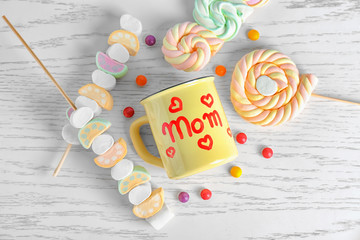 Metal cup with word MOM and sweets for Mother's day on wooden background