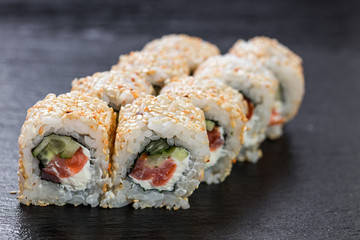 California roll with salmon arranged on slate plate background