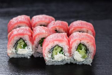 Philadelphia makizushi roll with tuna arranged on stone background
