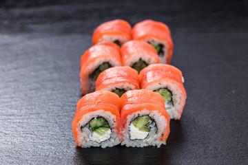 Smoked salmon philadelphia makizushi roll arranged on stone background