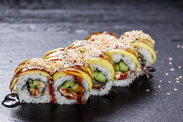 Green dragon makizushi roll with unagi seasoned with sauce over slate plate background