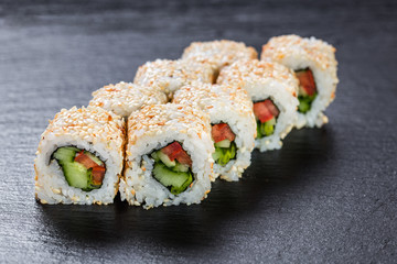 Vegeterian makizushi roll with cucumber and tomato over slate plate background