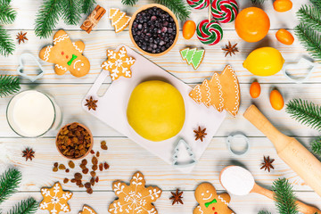 Cooking Christmas gingerbread cookies with the ingredients, dough, candy and winter spices decorating for new year celebration on white wooden table. Xmas food background