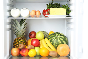 Open fridge full of fruits with cheese and bottle of milk