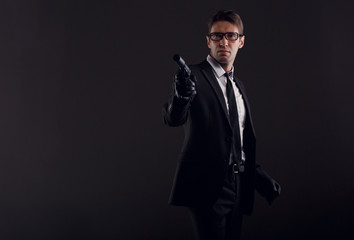 Picture of man in glasses and leather gloves with gun