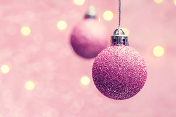 Photo of two Christmas pink balls on pink background with spots.