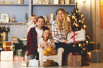 New Year's picture of happy family on background of Christmas decorations,pine