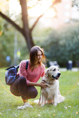 Picture of brunette with backpack on walk with retriever