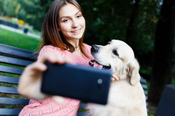 Image of brunette on bench making selfie with retriever