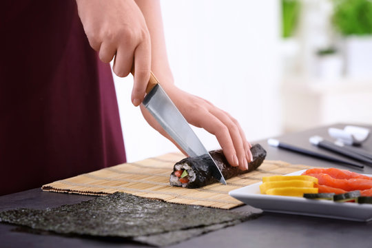 Young woman making sushi rolls at home