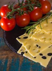 Yellow medium-hard mild Swiss cheese Emmental, fresh rosemary and cherry tomatoes