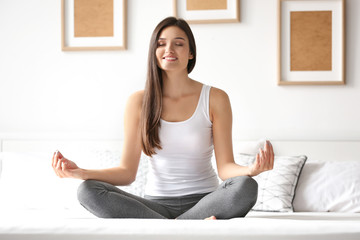 Young woman meditating in bed at home