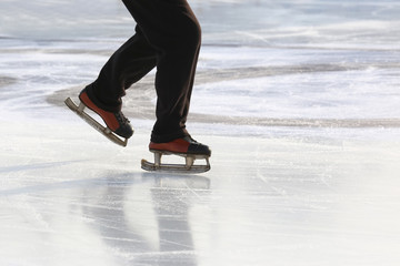 feet on the skates of a person rolling on the ice rink.