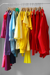 Rack with rainbow clothes on grey background
