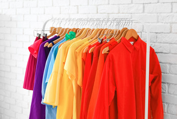 Rack with rainbow clothes near brick wall