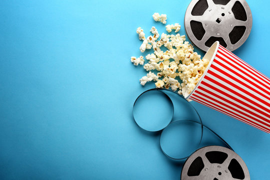 Composition with popcorn and cinema film on color background