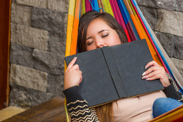 Close up of young beautiful woman sleeping in a hammock and holding a book with her hands, in blurred background