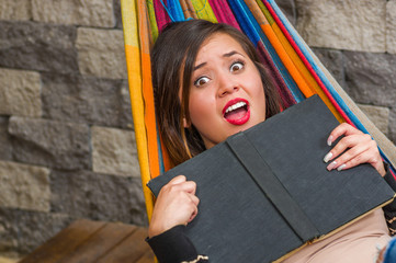 Close up of surprised young beautiful woman in a hammock and holding a book with her hands, in blurred background