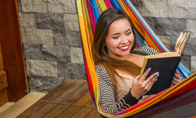 Close up of smiling young beautiful woman reading a book in a hammock, in blurred background