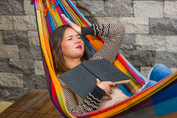 Close up of young beautiful woman with a headache touching her head using her hand and relaxing in a hammock, while is holding a book with her other hand, in a blurred background