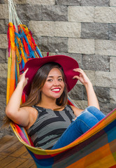 Close up of young beautiful woman relaxing in a hammock and wearing a red fashion hat holding with both hands, in blurred background