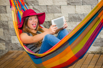 Close up of happy young beautiful woman wearing a red fashion hat and relaxing in a hammock and taking a selfie with her tablet, in blurred background