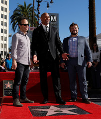 Actor Johnson poses on his star with actor Black and director Kasdan after it was unveiled on the Hollywood Walk of Fame in Los Angeles