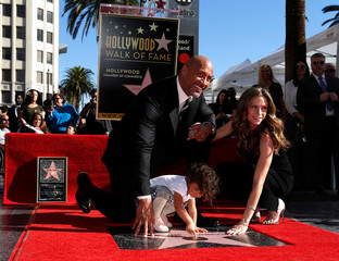 Actor Johnson poses on his star with Lauren Hashian and their daughter Jasmine Lia after it was unveiled on the Hollywood Walk of Fame in Los Angeles