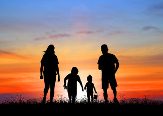 silhouette family  walking on blurry colorful sky at sunset time