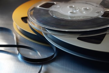 Still life of reel-to-reel audio tape on a metallic surface.