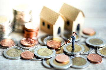 Miniature People Happy Couple Standing with Stack Coins White Background and Tiny Model House