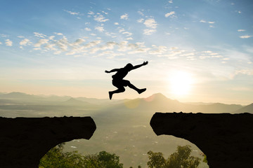 Man jump Mountain cliff sun light over silhouette Wall mural