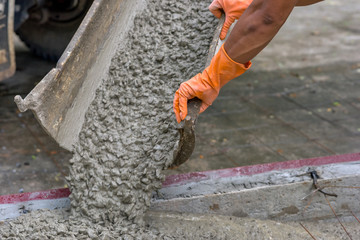 Concrete pouring during commercial concreting floors and worker is working