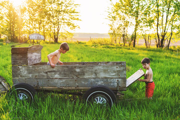 Two boys playing with an old farm wagon