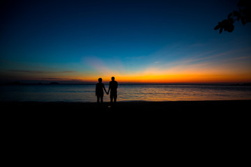 male and female silhouette holding hands by the sea with light Twilight.