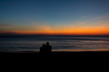 Male silhouette woman sitting hugging at the seaside with twilight