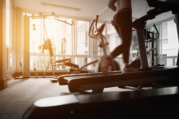 Woman running in a gym on a treadmill concept for exercising, fitness and healthy lifestyle. movement action with vintage filter.