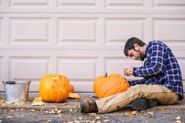 Man sitting outdoors carving a Halloween pumpkin
