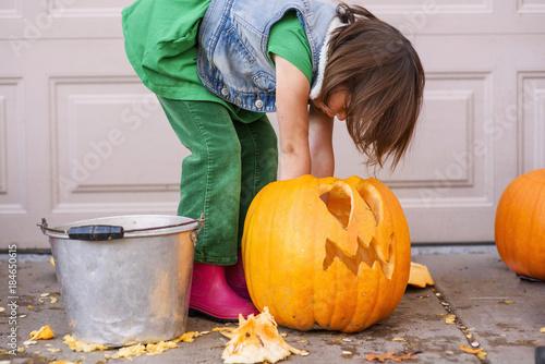Girl carving a Halloween pumpkin
