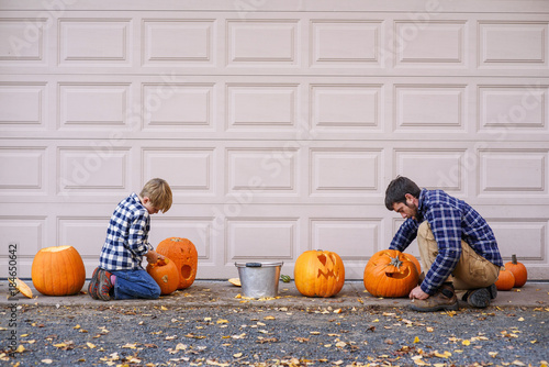 Father and son sitting by a garage door carving Halloween pumpkins