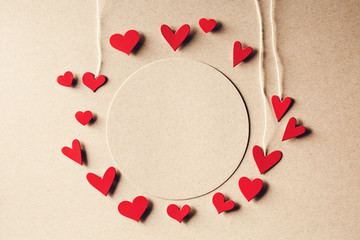 Handmade small paper hearts with strings on erthy colored paper background