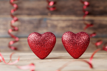 Two glitter hearts on vintage wooden table. Saint Valentines day greeting card. 14 February background.