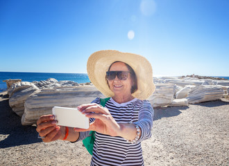 Mature beautiful woman traveler takes pictures on mobile phone. Travel to Greece and Turkey, the monuments of ancient architecture, active seniors
