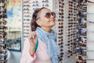 A beautiful stylish elderly woman chooses sunglasses in an optics store. Beauty and fashion, active seniors
