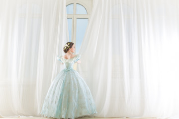 Elegant woman at a high window in historic dress, straightens the curtains, waiting friends