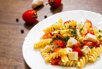 Fusilli pasta salad with cherry tomatoes and cheese in a plate on wooden table